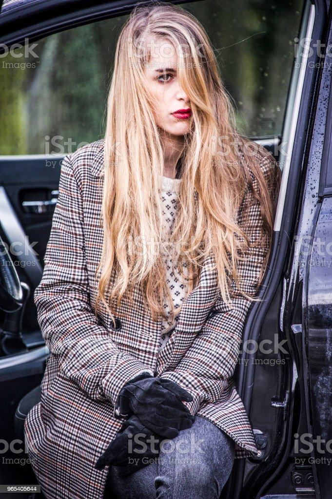 時髦的年輕女子正坐在一輛開著門的汽車裡, 腿出來了。 - 免版稅下垂圖庫照片