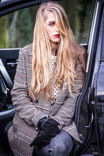 時髦的年輕女子正坐在一輛開著門的汽車裡 腿出來了 照片檔及更多 下垂 照片