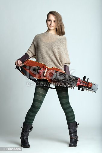 Trendy young woman musician with modern hairstyle wearing tights holding a modern reconstruction of a medieval Swedish nyckelharpa over white