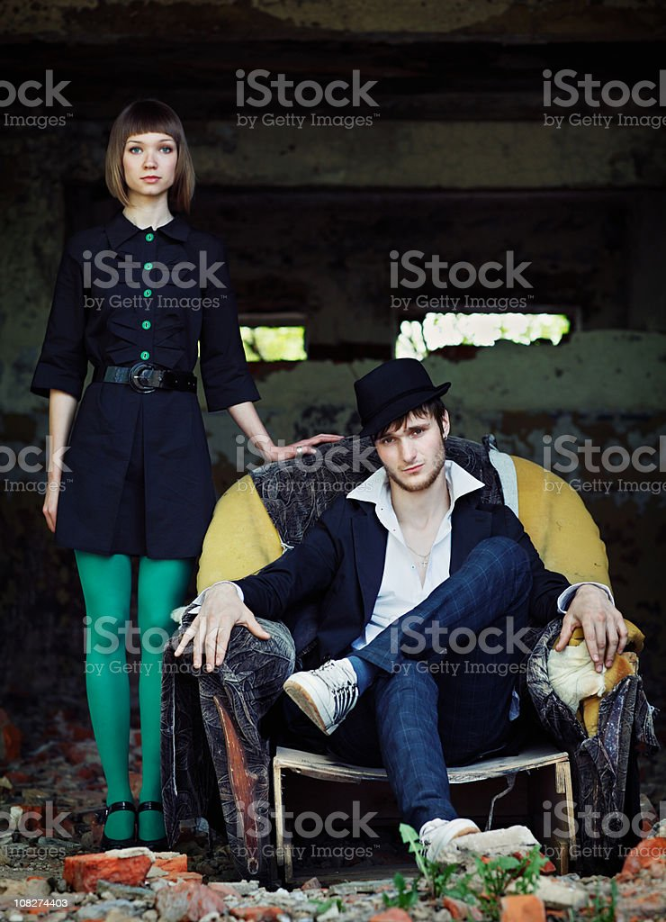 Trendy Young Woman Stands Beside Man Sitting in Chair Outside royalty-free stock photo