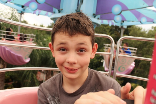Ten year old boy, very unsure, while riding a spinning amusement park ride.