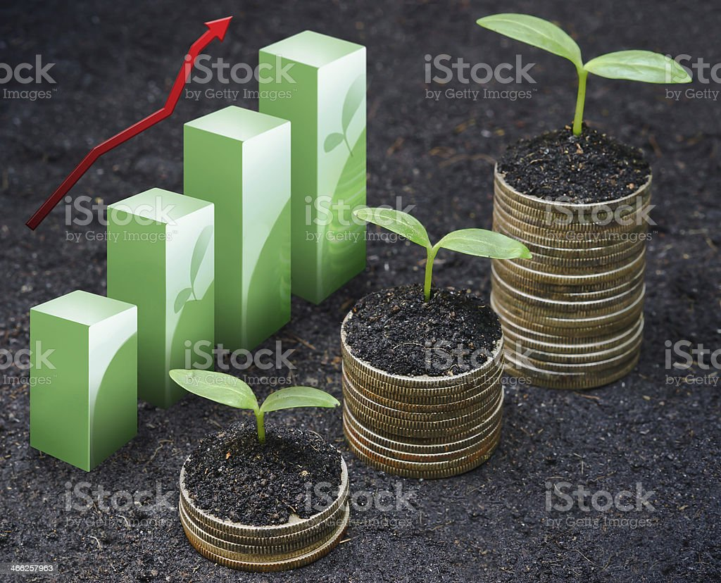 tress growing on coins with green graph stock photo