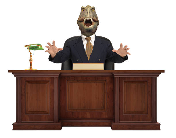 T-Rex head on a businessman's body sitting behind a desk A classic styled corporate desk with with a Tyrannosaurus Rex sitting behind it wearing a suit and tie on white background miserly stock pictures, royalty-free photos & images