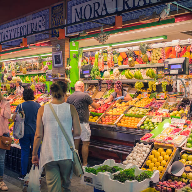 Mercado de Triana, Seville People visiting the historical Mercado de Triana, a market hall in Seville, Spain. market hall stock pictures, royalty-free photos & images