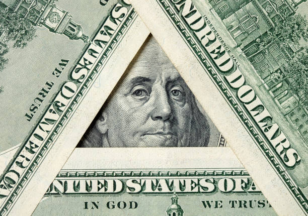 Triangle made of $100 bills with Benjamin Franklin inside Triangle made of $100 banknotes with Benjamin Franklin portrait inside. conspiracy stock pictures, royalty-free photos & images