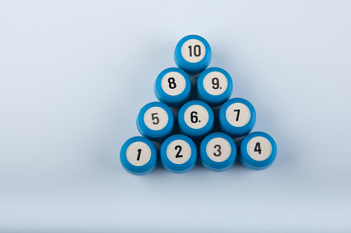 Triangle made of plastic lotto kegs with numbers lay on white background