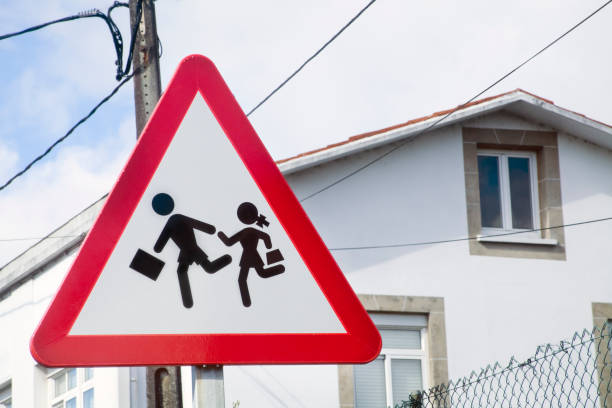 Triangle pedestrians road sign, school building nearby stock photo
