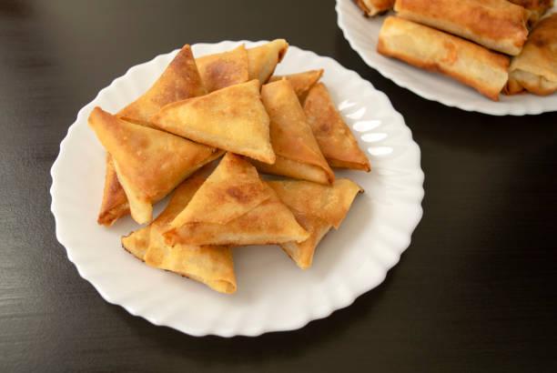Triangular arabic chicken samosa and spring rolls on dark wooden background stock photo