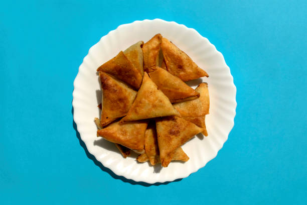 Triangular arabic chicken samosa on bright blue background stock photo