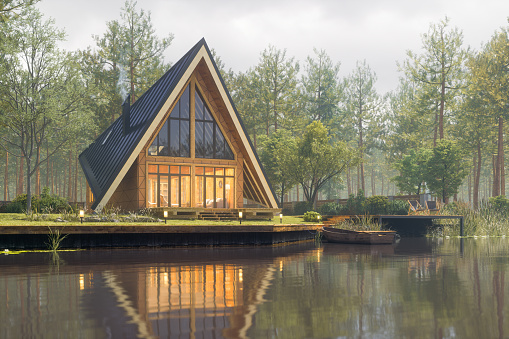Triangular modern lake house in a misty forest at fall.