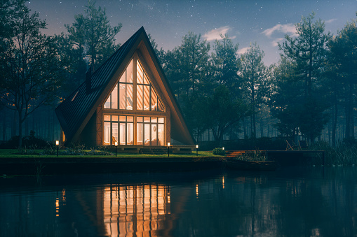 Triangular modern lake house in a misty forest at night.