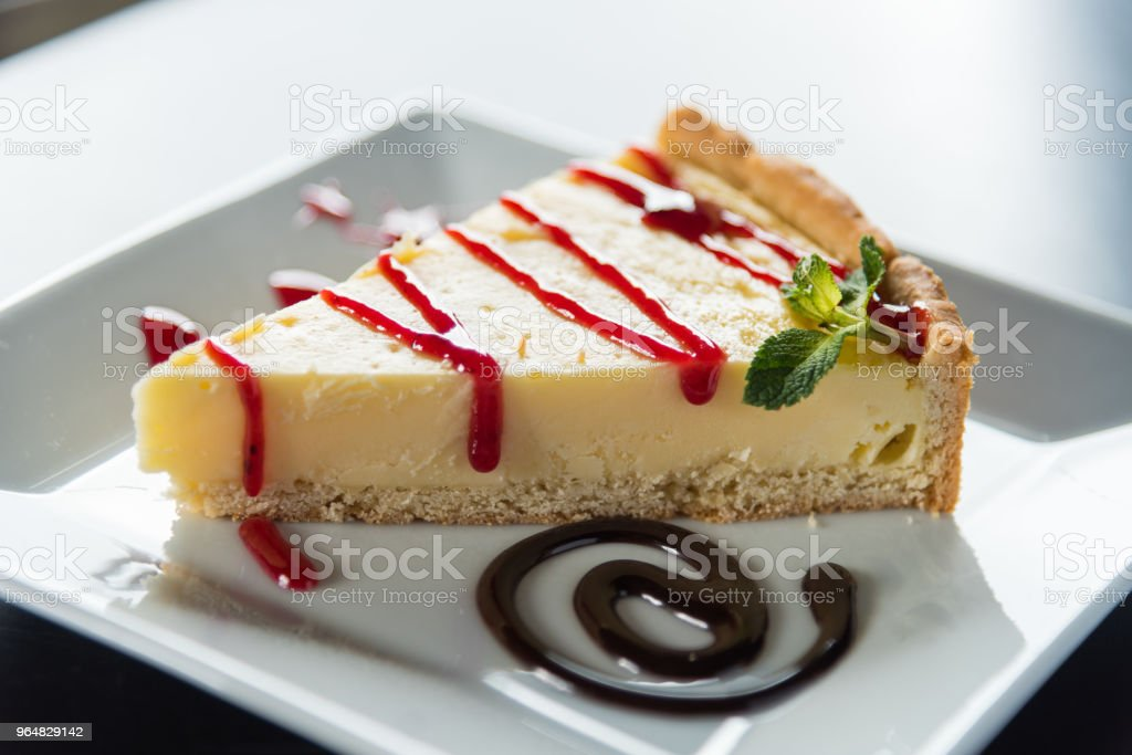 Triangular piece of cheesecake on a white plate decorated with mint and berry jam. royalty-free stock photo