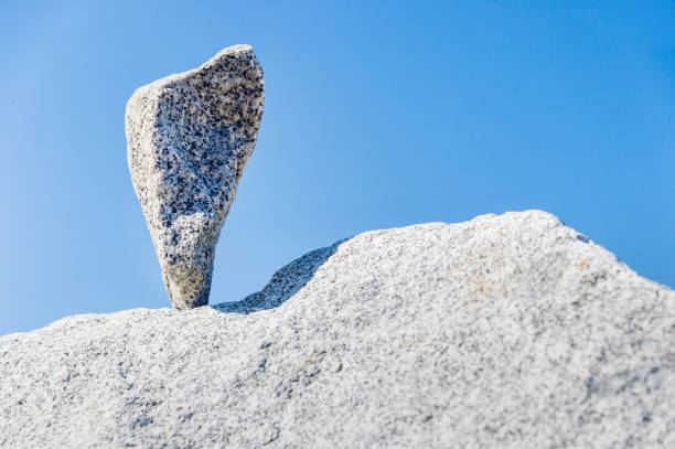Triangular rock balanced on the tip in Vancouver rock stacking garden stock photo