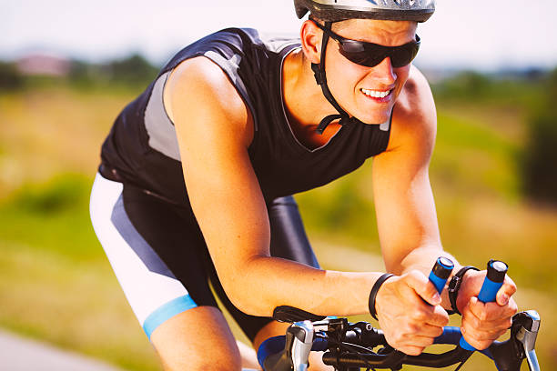 triathlete cycling on a bicycle - young singles stock photos and pictures