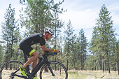 Male Caucasian cyclist races during the bicycling stage of a triathlon. He is on a highway out in a rural area surrounded by grass and pine trees,