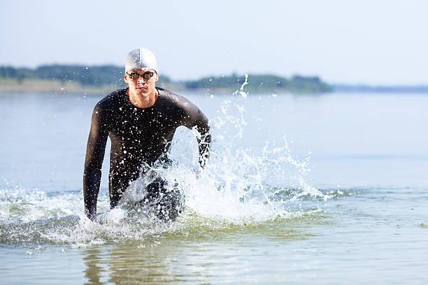 Triatleta corriendo fuera del agua - foto de stock