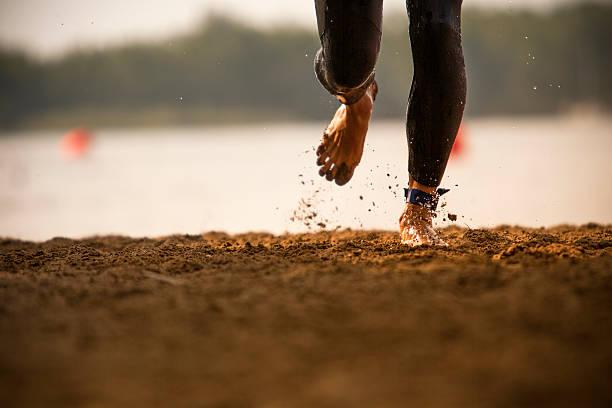 Triathlete runs out of a lake stock photo
