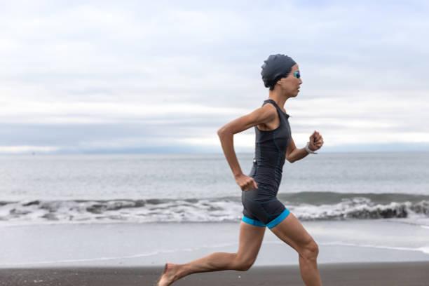 triathlete woman running on beach - showus стоковые фото и изображения