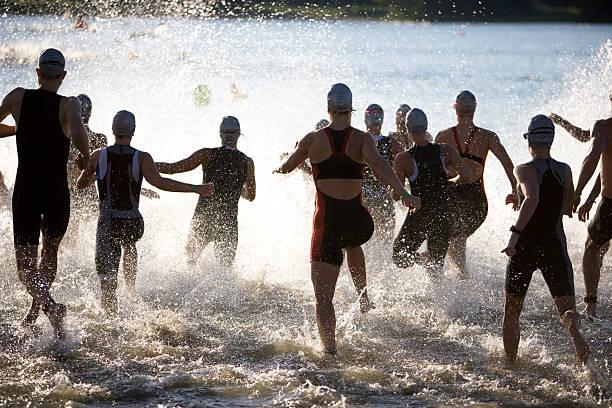 Triathletes al inicio de triatlón corriendo en el agua. - foto de stock