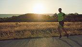 triathlon athlete running  on morning training sunrise in the background