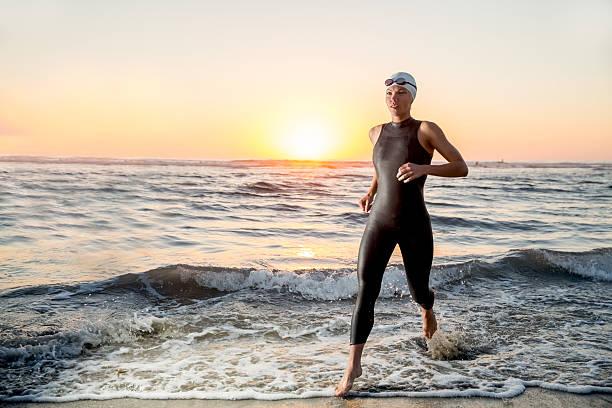 Triatlón atleta corriendo fuera del agua - foto de stock