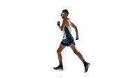 Triathlon male athlete running isolated on white studio background. Caucasian fit jogger, triathlete training wearing sports equipment. Concept of healthy lifestyle, sport, action, motion. Side view.