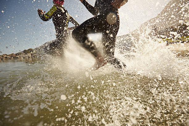 Triatlón participantes corriendo en el agua para nadar parte - foto de stock
