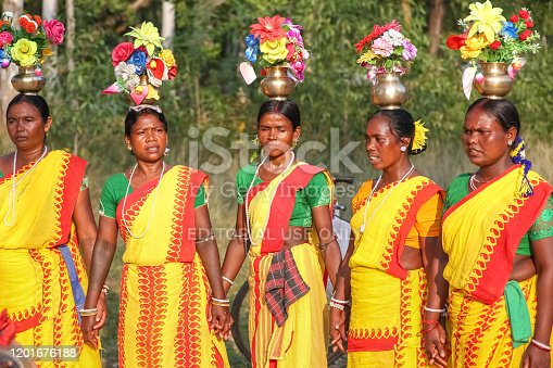 West Bengal, India, November 2,2019: Tribal women in traditional costumes perform folk dance in a forested area at Bolpur Shantiniketan, West Bengal