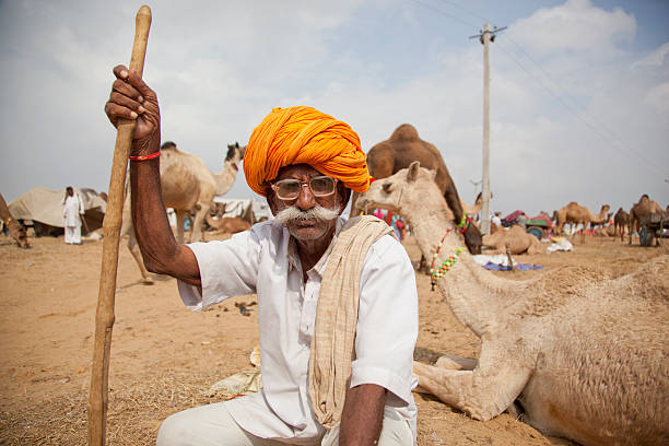 Tribal man in turban with camels Rajasthan India stock photo
