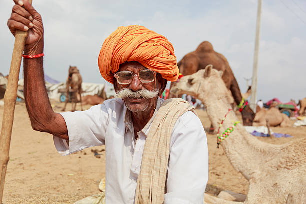 Tribal man with cane at camel fair Rajasthan India stock photo