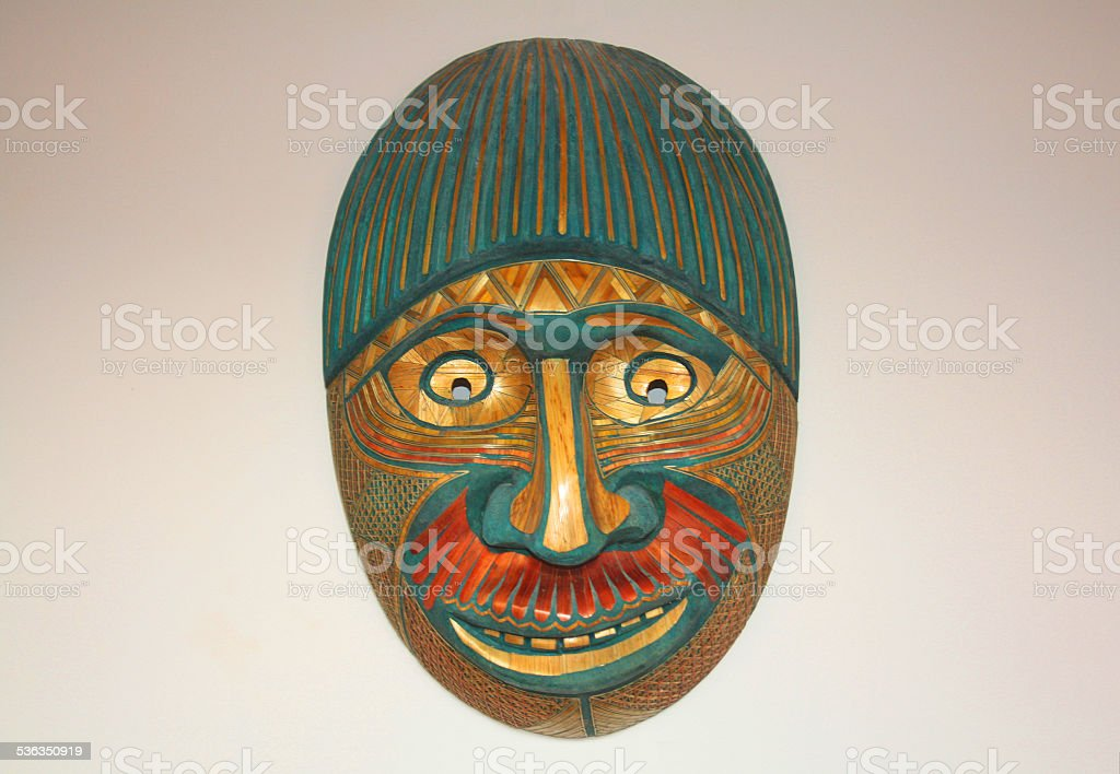Tribal mask hung in white wall stock photo