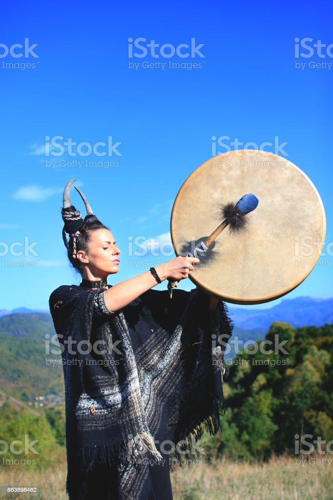 Tribal Pagan Woman with antlers playing a buffalo shamanic drum on the mountain stock photo