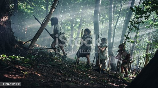 841481956 istock photo Tribe of Hunter-Gatherers Wearing Animal Skin Holding Stone Tipped Tools, Explore Prehistoric Forest in a Hunt for Animal Prey. Neanderthal Family Hunting in the Jungle or Migrating for Better Land 1194512906