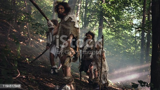 841481956 istock photo Tribe of Hunter-Gatherers Wearing Animal Skin Holding Stone Tipped Tools, Explore Prehistoric Forest in a Hunt for Animal Prey. Neanderthal Family Hunting in the Jungle or Migrating for Better Land 1194512945