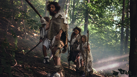 istock Tribe of Hunter-Gatherers Wearing Animal Skin Holding Stone Tipped Tools, Explore Prehistoric Forest in a Hunt for Animal Prey. Neanderthal Family Hunting in the Jungle or Migrating for Better Land 1194512945