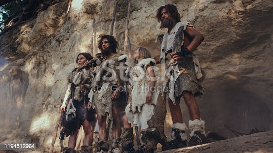841481956 istock photo Tribe of Hunter-Gatherers Wearing Animal Skin Holding Stone Tipped Tools, Stand Near Cave Entrance. Neanderthal Family Ready for Hunting in the Jungle or Migration 1194512964