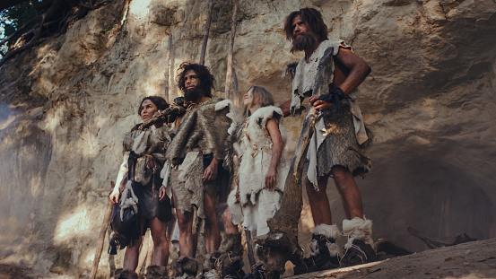 istock Tribe of Hunter-Gatherers Wearing Animal Skin Holding Stone Tipped Tools, Stand Near Cave Entrance. Neanderthal Family Ready for Hunting in the Jungle or Migration 1194512964
