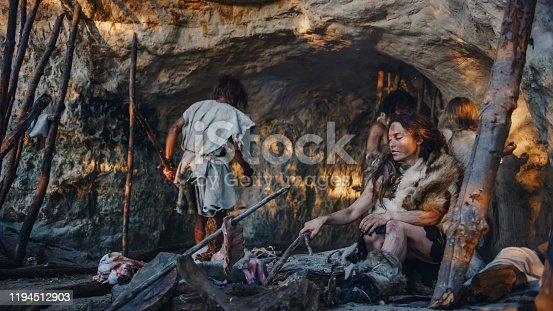 istock Tribe of Hunter-Gatherers Wearing Animal Skin Live in a Cave. Leader Brings Animal Prey from Hunting, Female Cooks Food on Bonfire, Girl Drawing on Wals Creating Art. Neanderthal Homo Sapiens Family 1194512903