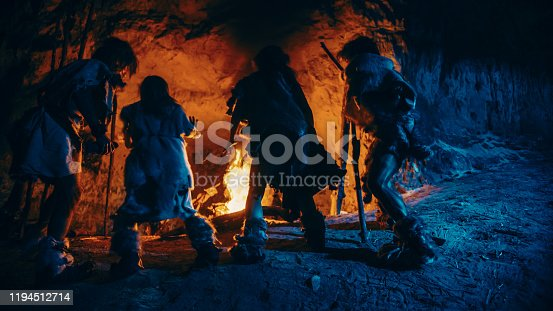 841481956 istock photo Tribe of Prehistoric Hunter-Gatherers Wearing Animal Skins Dance Around Bonfire Outside of Cave at Night. Neanderthal / Homo Sapiens Family Doing Pagan Religion Dancing Near Fire Back View Slow Motion 1194512714