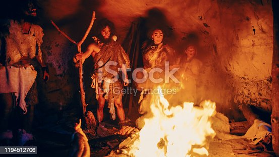 841481956 istock photo Tribe of Prehistoric Hunter-Gatherers Wearing Animal Skins Stand Around Bonfire Outside of Cave at Night. Portrait of Neanderthal / Homo Sapiens Family Doing Pagan Religion Ritual Near Fire 1194512706