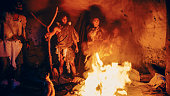 istock Tribe of Prehistoric Hunter-Gatherers Wearing Animal Skins Stand Around Bonfire Outside of Cave at Night. Portrait of Neanderthal / Homo Sapiens Family Doing Pagan Religion Ritual Near Fire 1194512706
