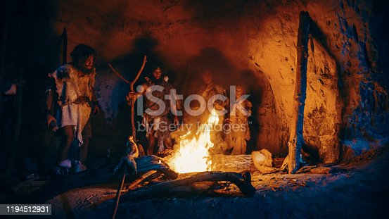 841481956 istock photo Tribe of Prehistoric Hunter-Gatherers Wearing Animal Skins Stand Around Bonfire Outside of Cave at Night. Portrait of Neanderthal / Homo Sapiens Family Doing Pagan Religion Ritual Near Fire 1194512931