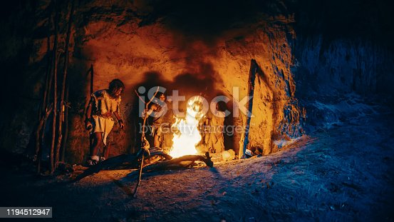841481956 istock photo Tribe of Prehistoric Hunter-Gatherers Wearing Animal Skins Stand Around Bonfire Outside of Cave at Night. Portrait of Neanderthal / Homo Sapiens Family Doing Pagan Religion Ritual Near Fire 1194512947