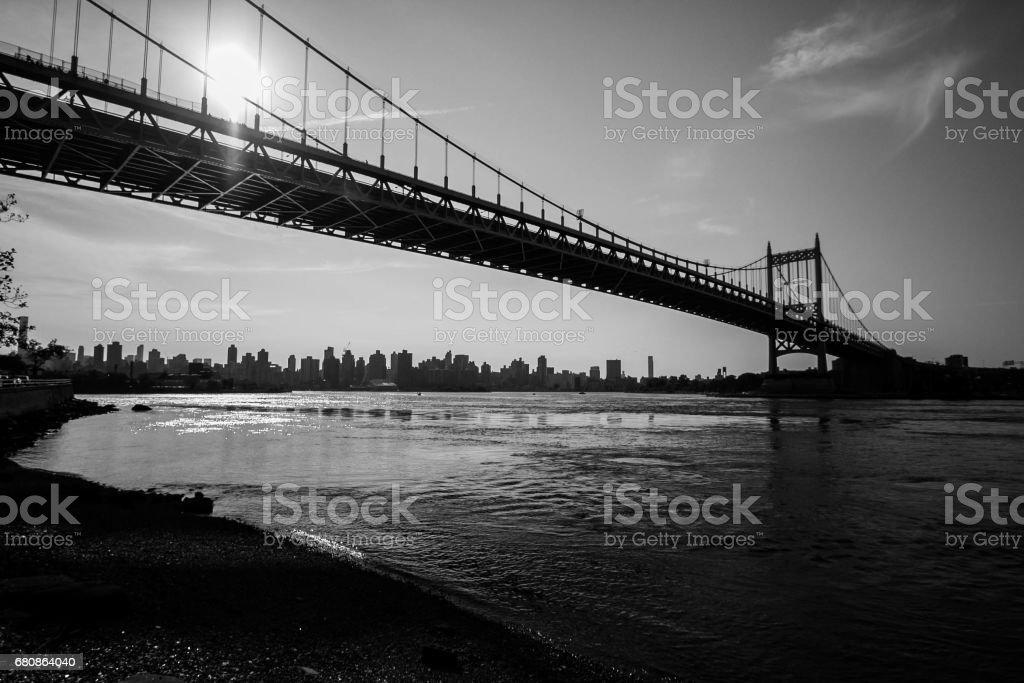Triborough bridge and dark shore in black and white stock photo