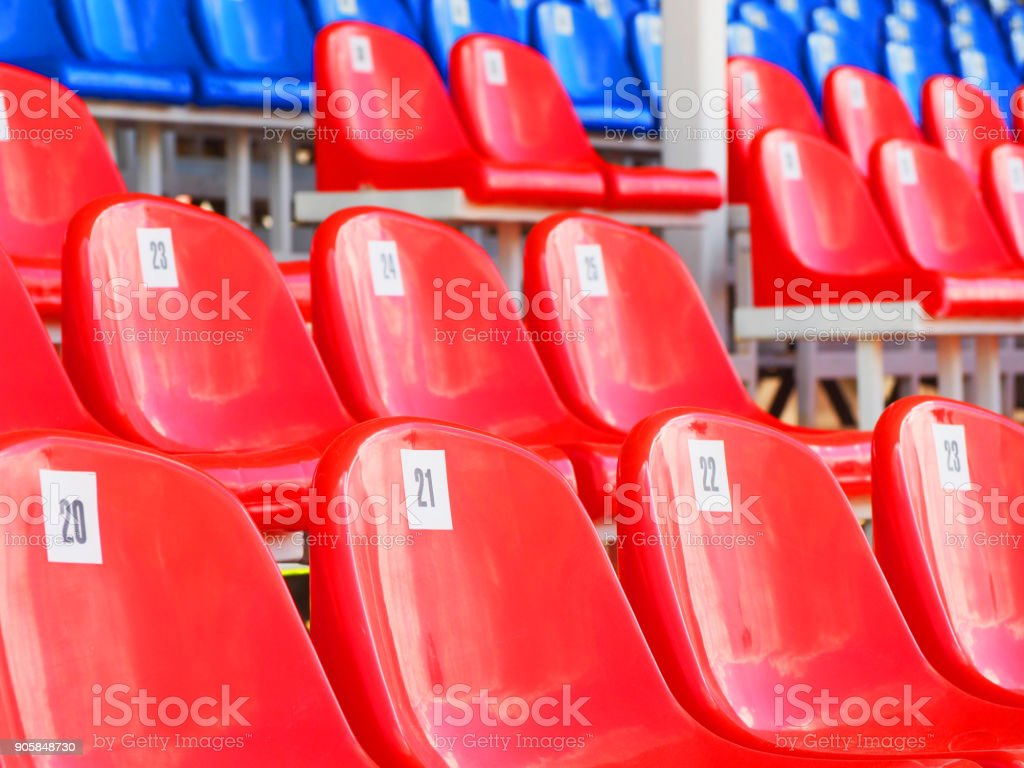 Tribune of stadium. Red and blue numbered empty plastic armchairs. Seats for spectators stand in a row. Passage between tribunes stock photo