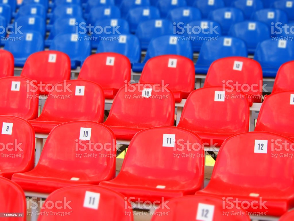 Tribune of stadium. Red and blue numbered empty plastic armchairs. Seats for spectators stand in a row stock photo