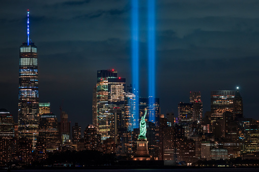 New Jersey - September 11, 2020, The Tribute in Light 9/11 memorial with the Statue of Liberty. New York City, USA