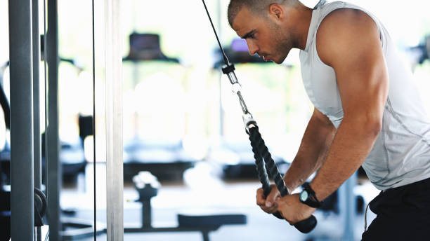 Triceps extension exercise. Closeup side view of late 20's muscular man doing cable extension exercise at the gym. He's pulling it downwards and isolating his triceps. He's highly focused during this exercise. exercise machine stock pictures, royalty-free photos & images