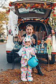 Trick o trunk. Siblings brother and sister celebrating Halloween in trunk of car. Children kids boy and baby girl celebrating October holiday outdoor. Social distance and safe alternative celebration