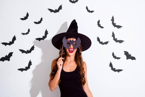 trick oder bedrohung! in der nähe porträt der stets gut gelaunte frau mit lockigen moderne frisur halten sie maske auf stick und machen sie toothy lächeln isoliert auf weißem hintergrund. - vampir schminken frau stock-fotos und bilder